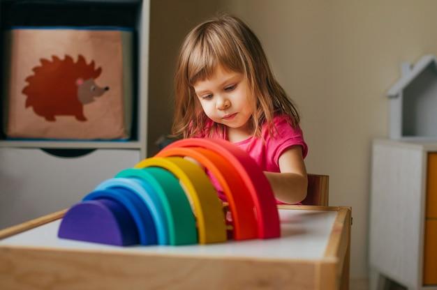 Koncepcja drewnianych zabawek bez plastiku. piękna mała dziewczynka bawi się tęczą kolorowe drewniane zabawki w pokoju dziecięcym