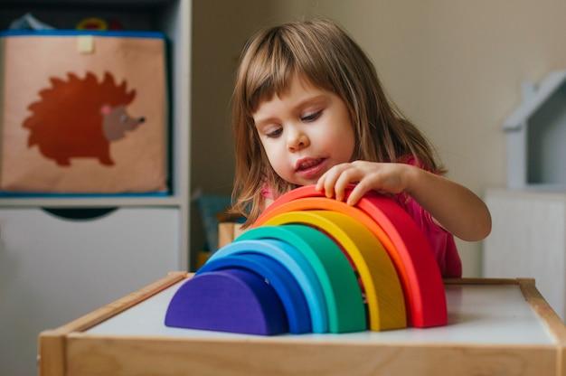 Koncepcja drewnianych zabawek bez plastiku. piękna mała dziewczynka bawi się tęczą kolorowe drewniane zabawki w pokoju zabaw