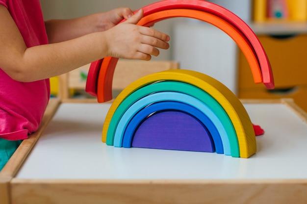 Koncepcja drewnianych zabawek bez plastiku. zbliżenie dziewczynki bawi się tęczy kolorowe drewniane zabawki w pokoju dziecięcym