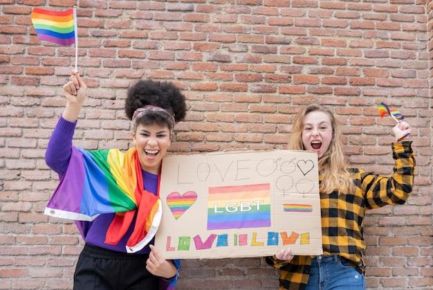 Koncepcja dumy lgbt. gejowski styl życia. prawdziwa para lesbijek przytulająca się i całująca z kultowym symbolem tęczy.