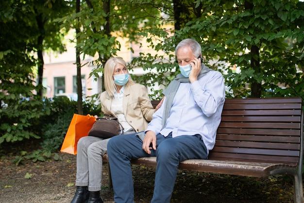 Koncepcja dystansowania się i separacji społecznej, zapobieganie koronawirusowi siedząc na ławce w koncepcji parku