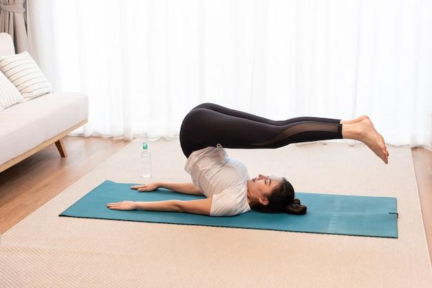 Koncepcja działalności produkcyjnej dopasowanie dziewczyna ubrana w biały t-shirt i czarne legginsy robi ćwiczenia pilates zwijające plecy.