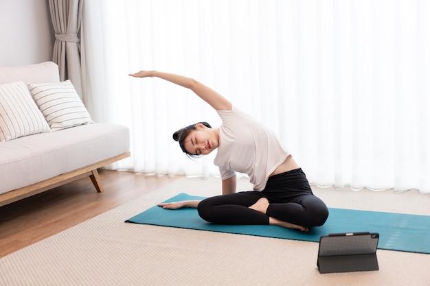 Koncepcja działalności produkcyjnej kobieta młody dorosły ubrany w biały t-shirt ćwiczy elastyczność swojego ciała, robiąc pilates mat.