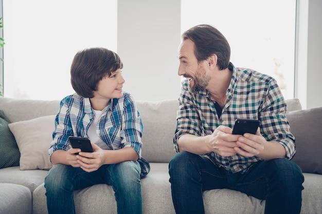 Koncepcja działań weekendowych. wesoły, brodaty tata oglądający przez telefon komiks, opowiadający swojemu podekscytowanemu potomstwu dowcipy i śmiejące się historie przez telefony siedzące na sofie w salonie
