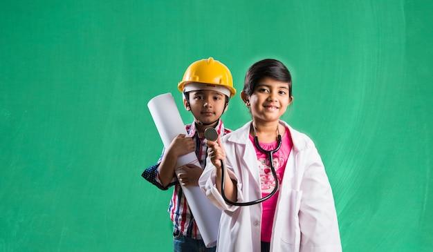 Koncepcja dzieci i edukacji - mały indyjski chłopiec i dziewczynka pozują przed tablicą z zieloną kredą w kostiumach inżynierów i stroju lekarza ze stetoskopem
