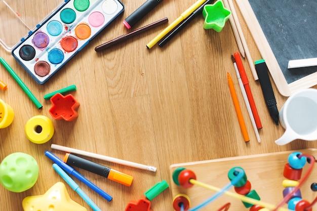 Koncepcja dzieci lub dzieci. zabawa zabawkami i materiały do rysowania na stole. widok z góry.