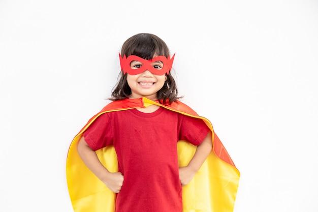 Koncepcja dzieci, uśmiechnięta dziewczyna grająca super bohatera na białym tle