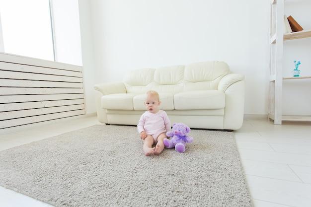 Koncepcja dzieciństwa, dzieci i niemowlęctwa - urocza blondynka dziecko siedzi na podłodze