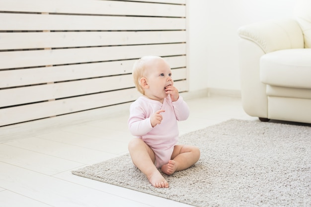 Koncepcja dzieciństwa i dzieci - śliczne urocze dziecko siedzi na podłodze