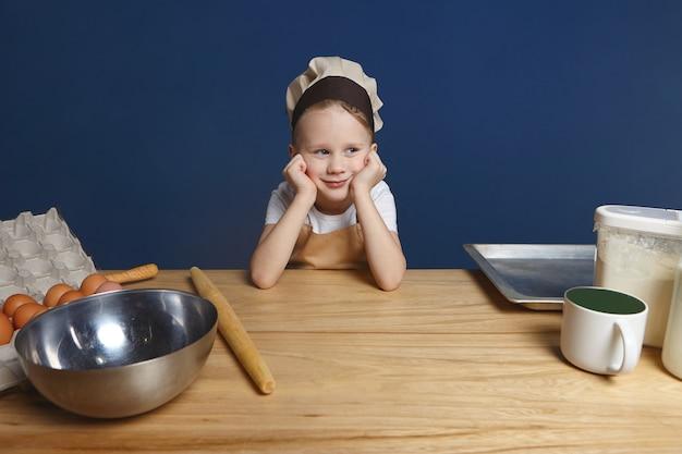 Koncepcja dzieciństwa, kuchni i gotowania. portret uroczego ślicznego chłopca