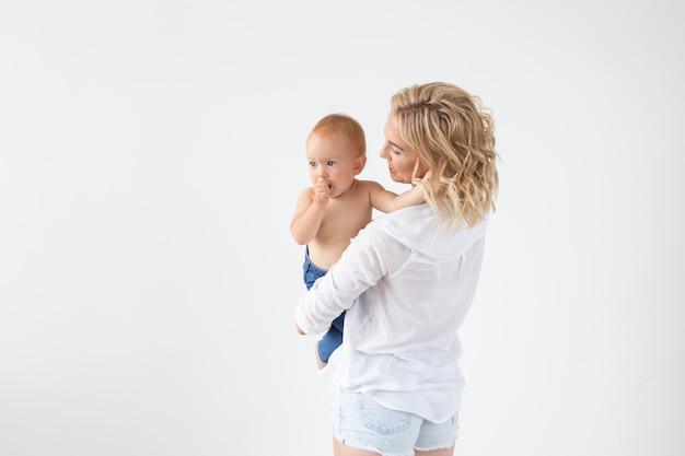 Koncepcja dzieciństwa, macierzyństwa i rodziny - portret szczęśliwa matka trzyma swoje dziecko na białym tle