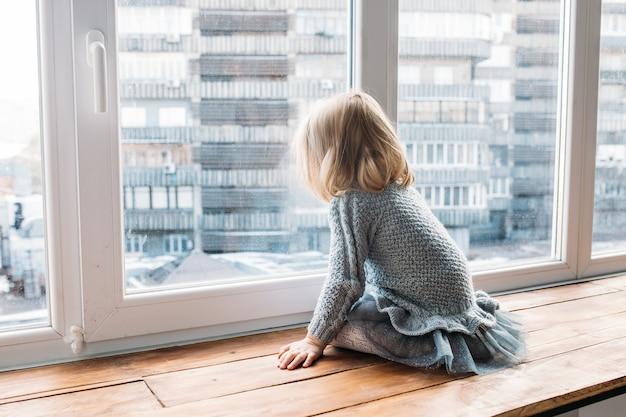 Koncepcja dzieciństwa. mała dziewczynka siedzi blisko okno w domu.