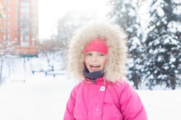 Koncepcja dzieciństwa, mody, pory roku i ludzi - 4k little girl playing in snow winter, view happy child making snowball, snowman par, kids in christmas vacation. twarz szczęśliwej dziewczyny w zimowych ubraniach