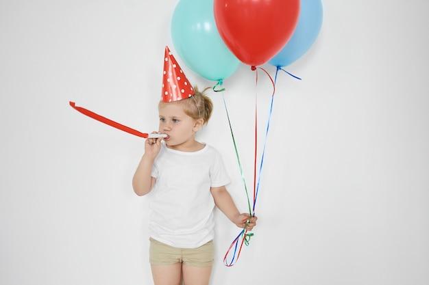 Koncepcja dzieciństwa, szczęścia, świętowania i zabawy. słodkie urocze małe dziecko dmucha w gwizdek, trzyma kolorowe balony, czuje się szczęśliwy, świętuje urodziny, pozuje na białej ścianie