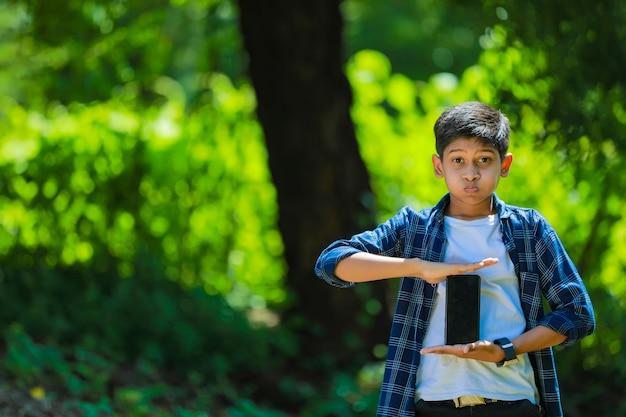Koncepcja dzieciństwa, technologii i ludzi - indyjski ładny chłopiec w szkole pokazuje smartfon z pustym ekranem