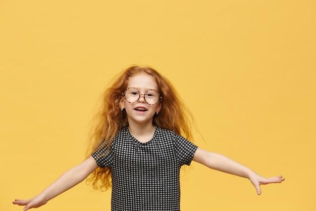 Koncepcja dzieciństwa, zabawy i radości. urocza, emocjonalna dziewczynka z obszernymi rudymi włosami wykrzykuje podekscytowany, skacze, trzymając szeroko ramiona, pozując przy pustej żółtej ścianie z miejscem na tekst