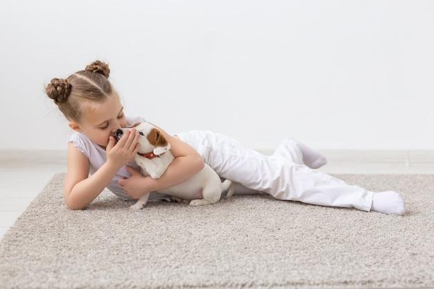 Koncepcja dzieciństwa, zwierzęta domowe i psy - mała dziewczynka dziecko pozuje na podłodze z szczeniakiem.