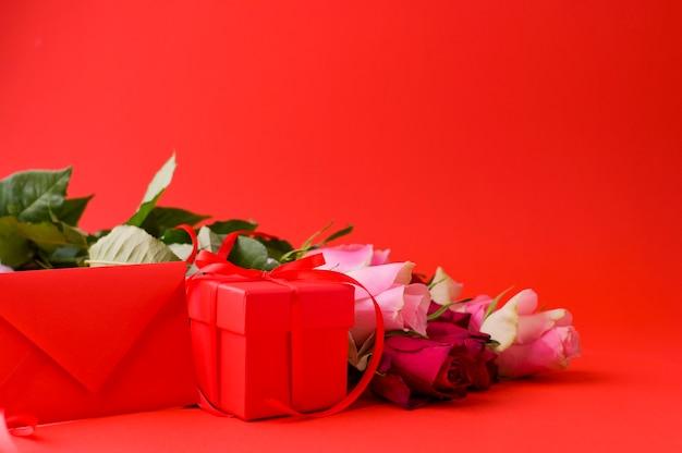 Koncepcja dzień kobiet i walentynki kartkę z życzeniami. kompozycja z prezentem, różami i kopertą. miejsce na tekst.