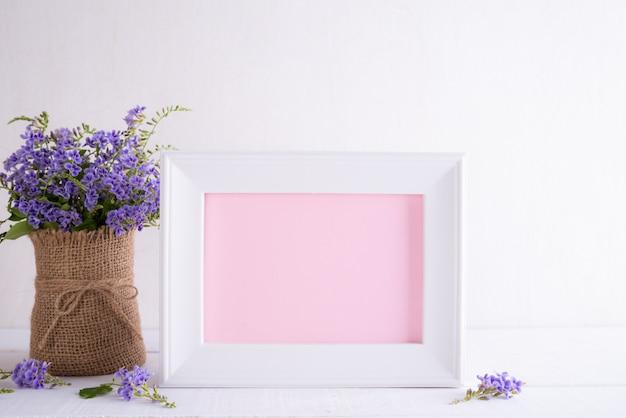 Koncepcja dzień matki happy. biała ramka na zdjęcia z pięknym purpurowym kwiatem w wazonie