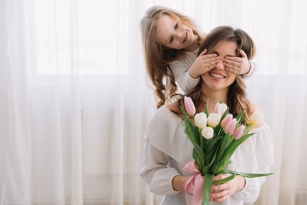 Koncepcja dzień matki szczęśliwy. córka dziecka gratuluje mamie i daje jej kwiaty tulipanów