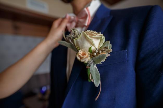 Koncepcja dzień ślubu. romantyczny moment na randce. ślub. panna młoda delikatnie gładzi pana młodego boutonniere i różowym motylem z bliska. kobieta poprawia motyla na koszuli mężczyzny.