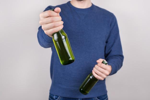 Koncepcja dzień świętego patryka. przycięte zbliżenie pijanego przystojnego pozytywnego faceta, trzymając w ręku butelkę smacznego świeżego piwa, rozciągając ramię na białym tle szara ściana