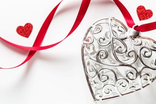 Koncepcja dzień świętego walentego, piękne srebrne serce z czerwonymi serduszkami ze wstążką
