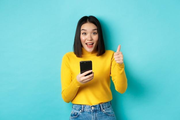 Koncepcja e-commerce i zakupów online. podekscytowana i zdumiona azjatka pokazująca kciuk w górę po użyciu aplikacji na smartfona, poleca urządzenie, stojąc nad niebieskim tłem.