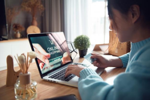 Koncepcja e-commerce i zakupów online, ręka kobiety za pomocą laptopa (strona internetowa makiety)