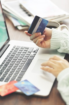 Koncepcja e-commerce. kobieta z kartą kredytową i laptopem, z bliska