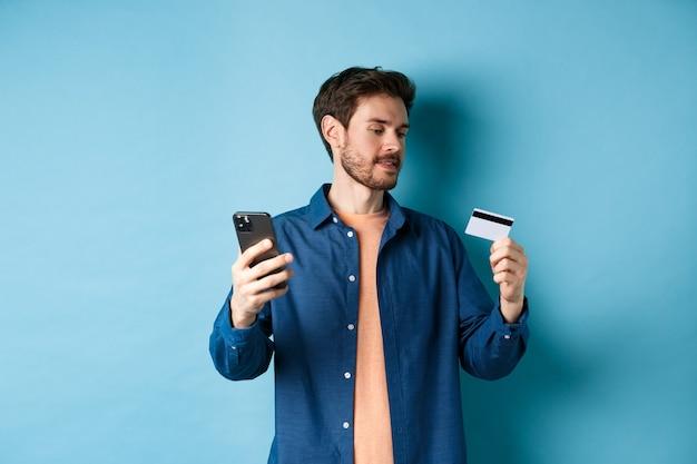 Koncepcja e-commerce. mężczyzna płaci za płatności online, odczytuje numer karty kredytowej i trzyma telefon komórkowy, stojąc na niebieskim tle.