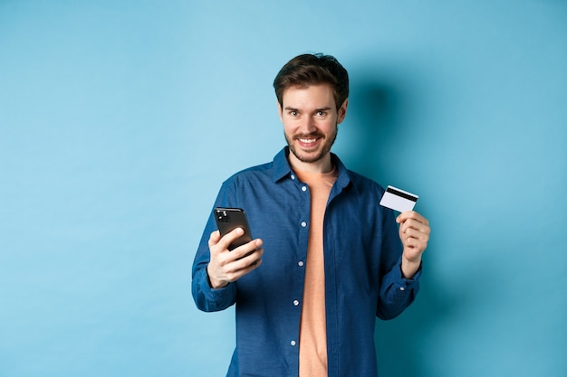 Koncepcja e-commerce. przystojny młody mężczyzna robi zakupy online, trzymając smartfon i plastikową kartę kredytową, uśmiechając się do kamery, stojąc na niebieskim tle.