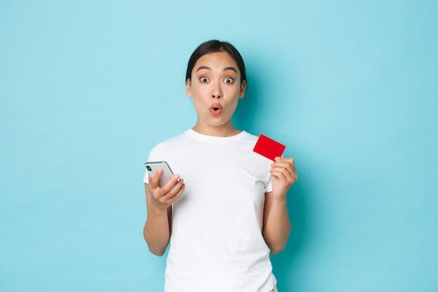 Koncepcja e-commerce, zakupów i stylu życia. podekscytowana uśmiechnięta azjatka dowiedziała się o specjalnym rabacie online, trzymając kartę kredytową i telefon komórkowy, używając aplikacji do składania zamówień, na jasnoniebieskim tle.