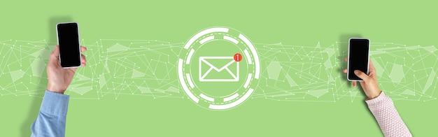 Koncepcja e-mail. ręce ze smartfonem na zielonym tle z grafiką.