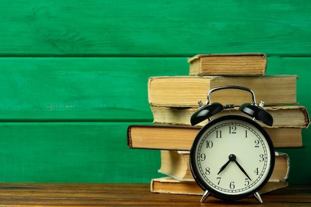 Koncepcja edukacji. czarny budzik vintage ze starymi książkami na stole.