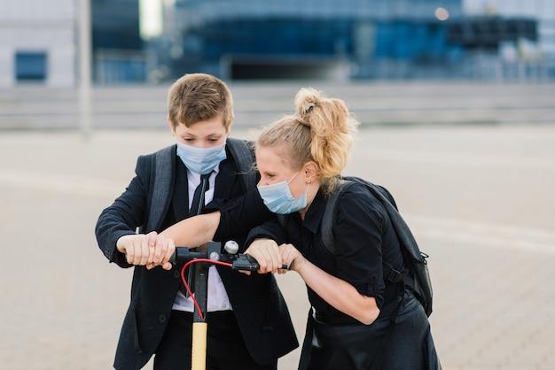 Koncepcja edukacji, dzieciństwa i ludzi. szczęśliwe dzieci w wieku szkolnym z plecakami i skuterami na zewnątrz w masce ochronnej