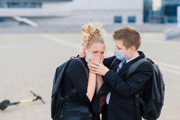 Koncepcja edukacji, dzieciństwa i ludzi. zdenerwowane dzieci w wieku szkolnym z plecakami i skuterami na zewnątrz w masce ochronnej