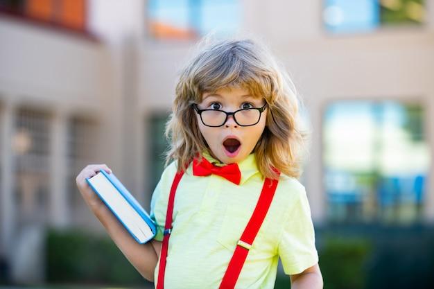 Koncepcja edukacji dziecka i czytania. słodkie dzieci w pobliżu szkoły na zewnątrz.