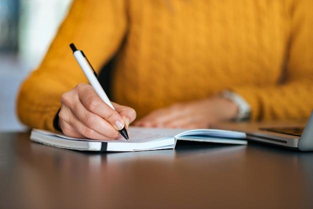 Koncepcja edukacji. dziewczyna robi notatkom. zbliżenie.