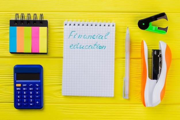 Koncepcja edukacji finansowej leżała płasko. notatnik z długopisem i innymi przedmiotami papierniczymi na żółtym drewnianym stole.