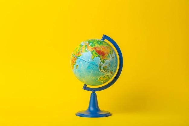 Koncepcja edukacji i globalizmu. kula ziemska na otwartej książce na stole w klasie uniwersyteckiej na żółtym tle