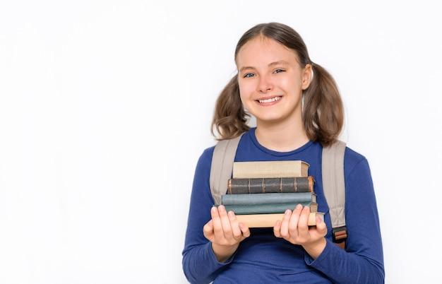 Koncepcja edukacji i powrotu do szkoły uśmiechnięta uczennica z podręcznikami i plecakiem na szarym tle