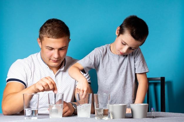 Koncepcja edukacji i studiów chemii. zbliżenie chłopca i jego ojca, naukowcy nalewają wodę do szklanki z pierwiastkami chemicznymi, do eksperymentów w domu
