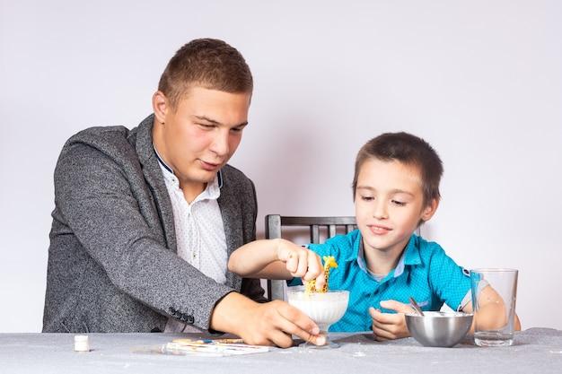 Koncepcja edukacji i szkolenia chemii. zbliżenie chłopca i jego taty, którzy robią domowe doświadczenie, przygotowują nienewtonowski płyn ze skrobi i wody