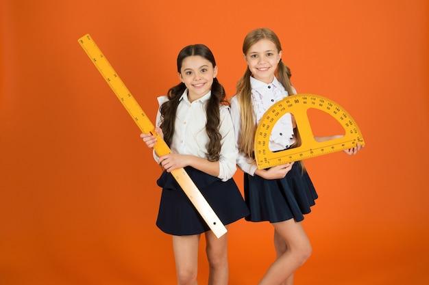 Koncepcja edukacji i szkoły. uczniowie uczący się geometrii. dzieci mundurek szkolny na pomarańczowym tle. dyscypliny szkolne stem. uczeń słodkie dziewczyny z dużymi władcami. ulubiony temat geometrii.