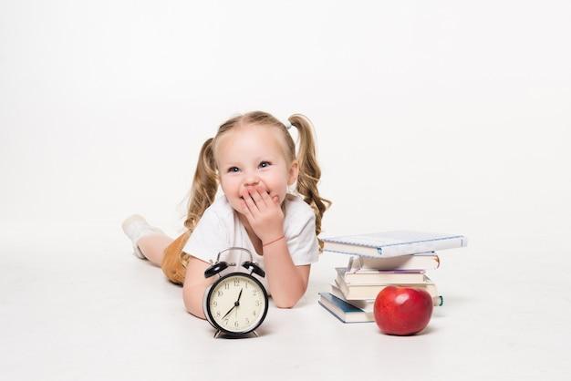 Koncepcja edukacji i szkoły. uśmiechnięta mała studencka dziewczyna z książkowym zegarem i jabłkiem na podłodze