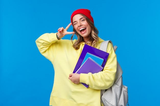 Koncepcja edukacji i uczenia się. wesoła, uśmiechnięta ładna studentka pokazująca gest pokoju, ciesząca się życiem studenckim, mrugająca oczami i optymistką, intensywnie studiująca, trzymająca zeszyty i plecak