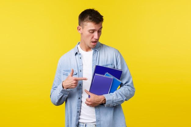 Koncepcja edukacji, kursów i uczelni. przystojny młody student płci męskiej wskazując palcem na notebooki i materiały do nauki, przygotować pracę domową do zadania na studia, żółte tło.