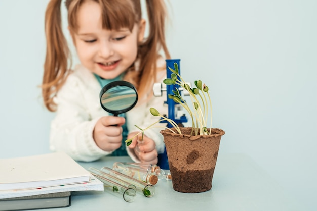 Koncepcja edukacji. mała dziewczynka spójrz na mikroskopy w laboratorium.