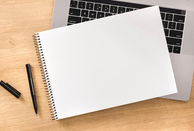 Koncepcja edukacji online pusty notatnik z laptopem i piórem na drewnianym blacie widok